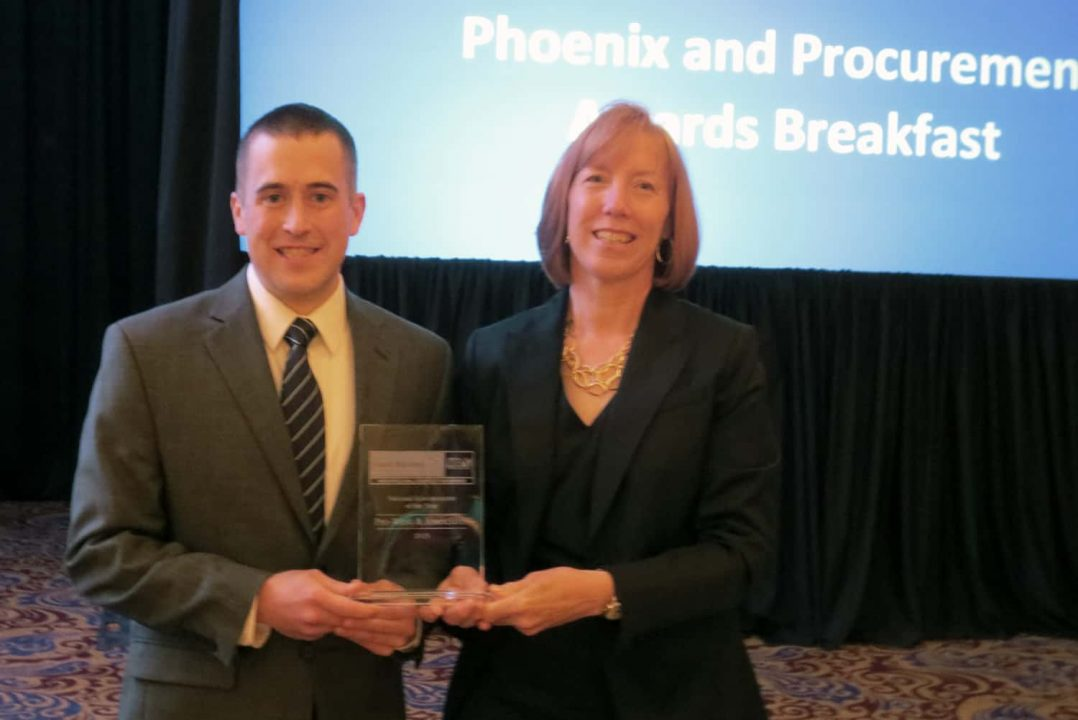 Annette Theroux and Kyle Heideman of Pro-West & Associates with the plaque representing the business' National Subcontractor of the Year Award.